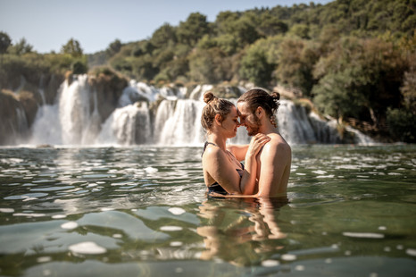 couple in water in krka nationalpark croatia - couple photos in front of a waterfall