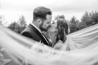 bridal couple kissing at the wedding in black and white