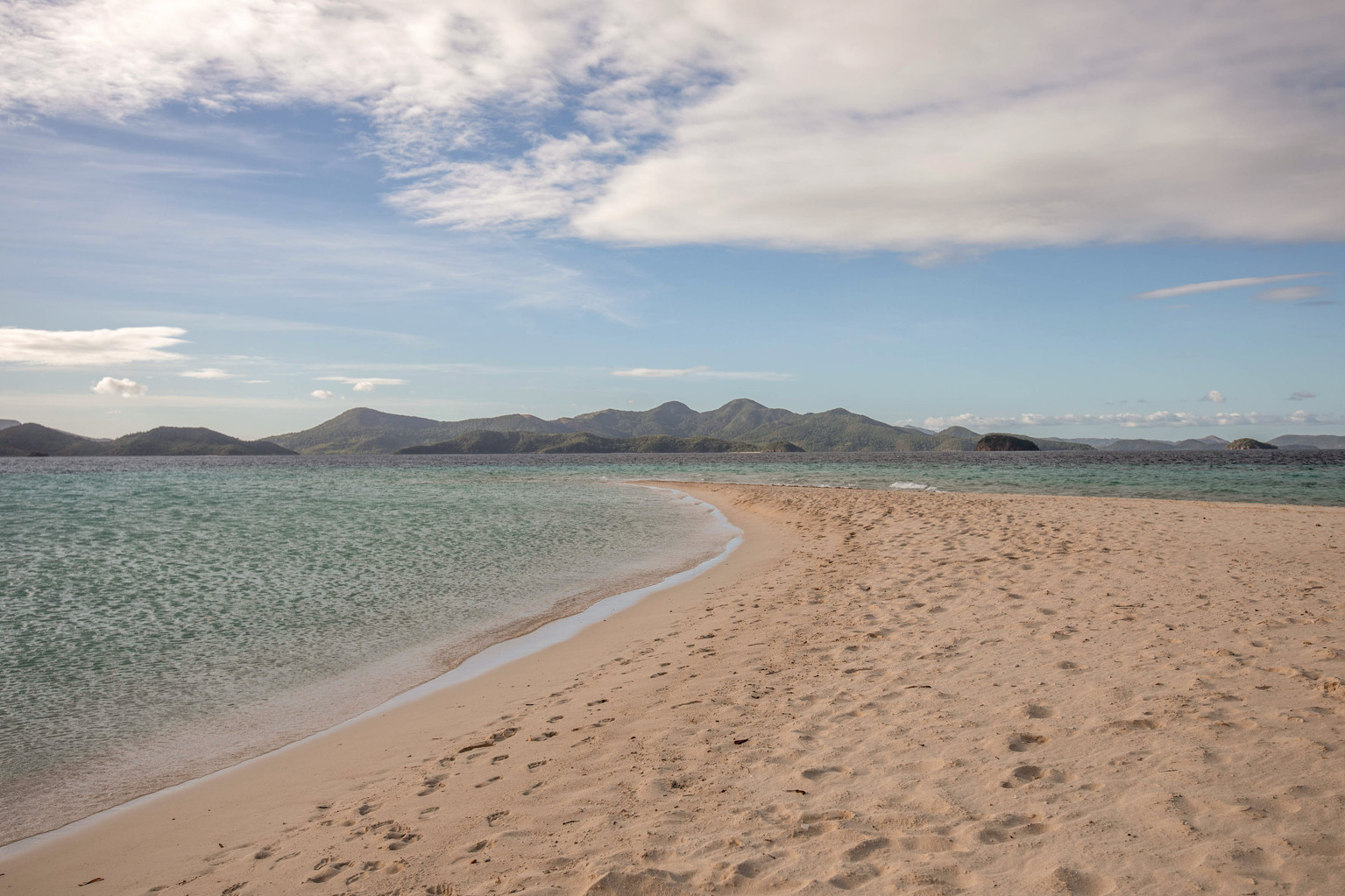 Sand beach and turquoises water in front of mountains in the philippines