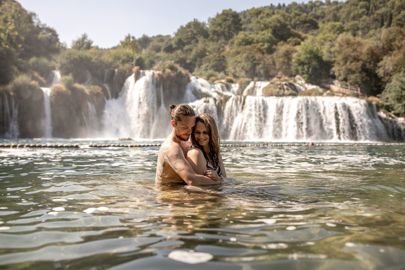 couple in a lake in front of a waterfall during this photo session in croatia