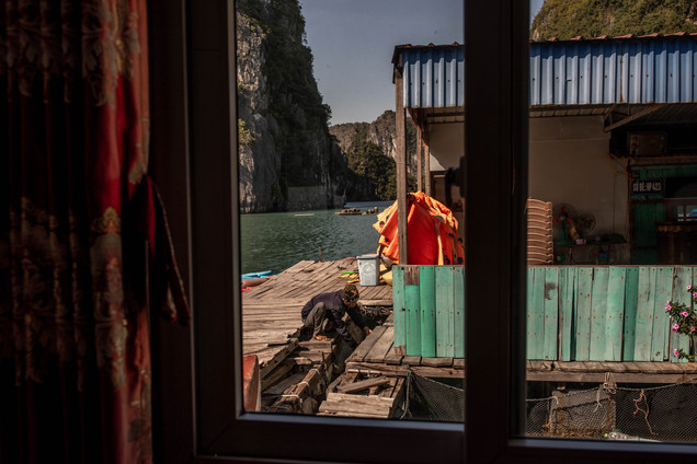 fischer man in a floating village in Ha Long Bay in Vietnam