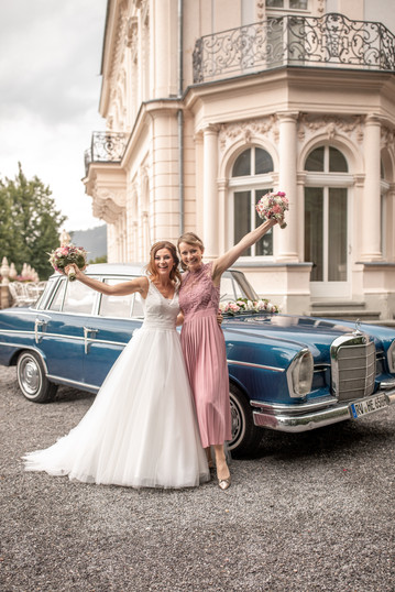 bridal and maid of honor in front of the wedding car having a lot of fun