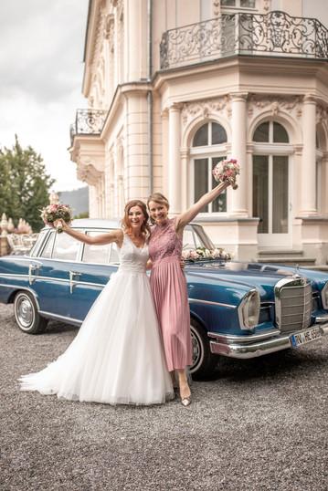 braut mit trauzeugin vor dem hochzeitsauto - hochzeitsfotografen in österreich in der nähe vom bodensee