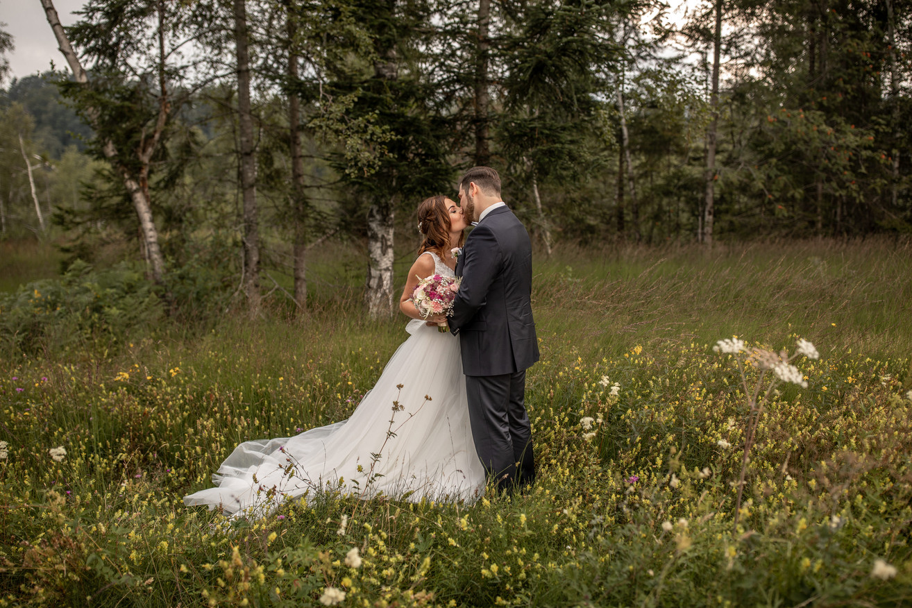 kissing bridal couple in the middle of gras - wedding photos special ones