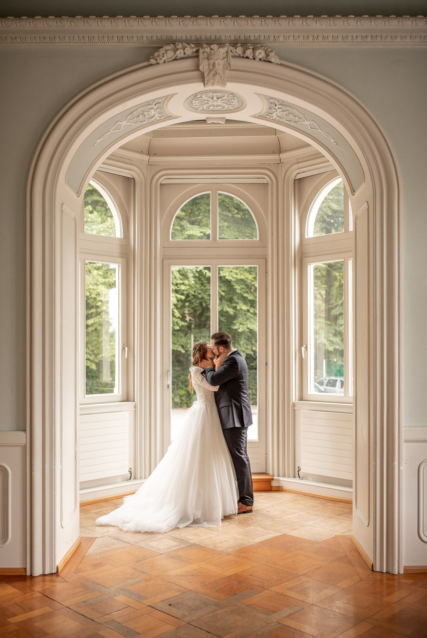bridal couple kissing in a beautiful building - wildembrace.photo