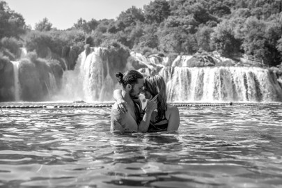 couplephotos in black and white in front of a big watterfall in croatia