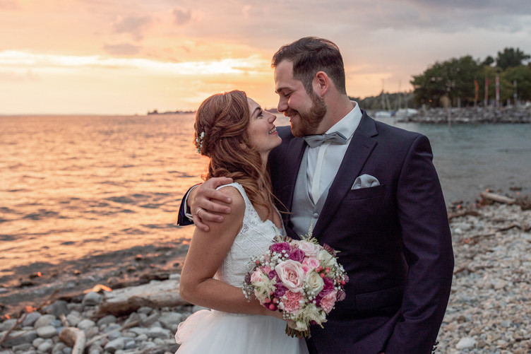 lovely bridal couple in front of lake of constance during the sunset