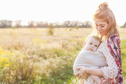 Little baby boy and his mother walking in the fields. Mother is holding and tickling her b