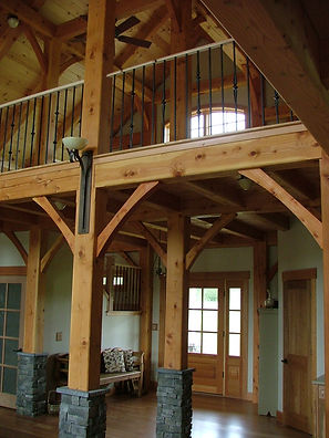 Timber frame cathedral entry with bridge by Timberworks Design
