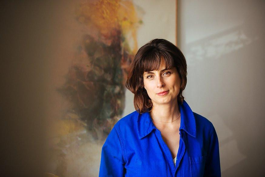 L'artiste Marie-Victoire Winkler porte une combinaison de travail bleu roi et pose devant un tableau coloré