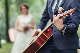 The groom plays the guitar for the bride