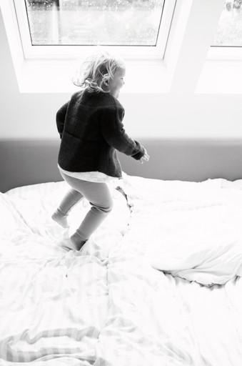 Mädchen hüpft auf dem Bett
