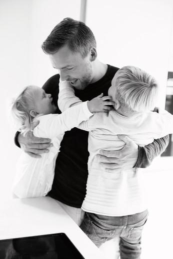 Geschwister umarmen Papa