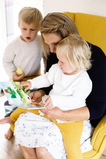 Mutter mit 2 Töchtern beim Buch vorlesen