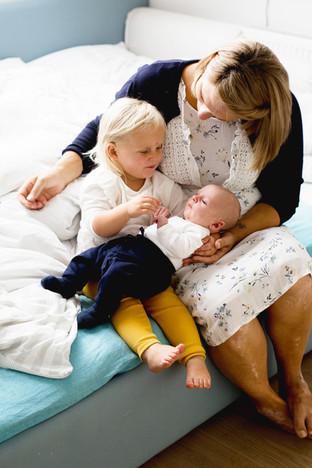 Mutter mit Tochter und Baby auf dem Bett sitzend