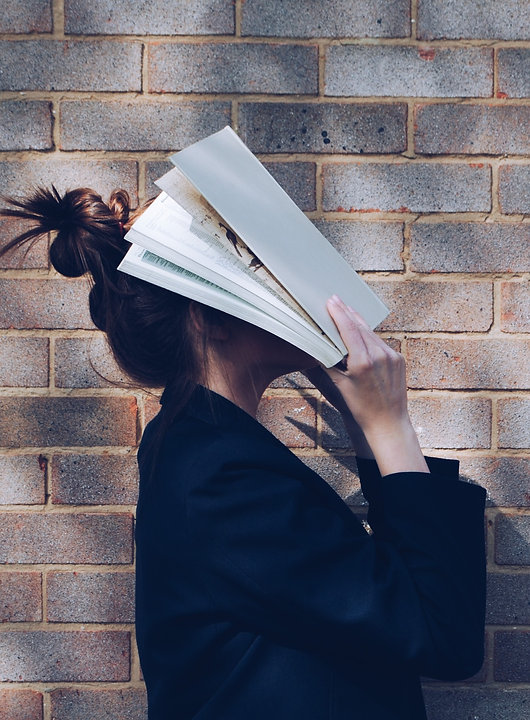 School Girl with Book in front of natural rustic red brick background holding book up to her face._e