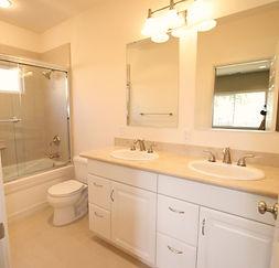 Light toned bathroom using Crema Marfil Stone ad a jetted tub