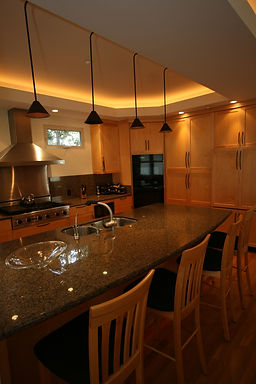 Kitchen with pendant lighs over the island and upward lights in the soffits