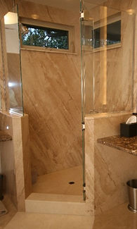 Stone slab shower with glass half walls and door