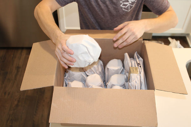 man using his hands to carefully pack a box with dishes