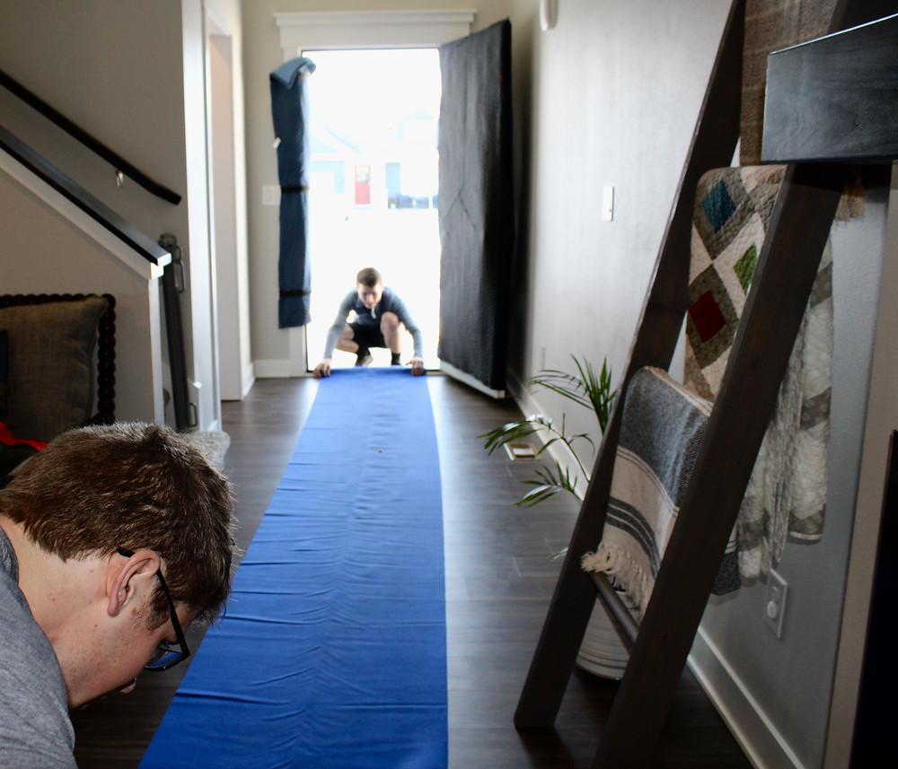 a pair of movers prepare a home for heavy foot traffic