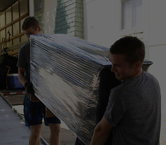 two professional movers carrying a wrapped couch into a moving truck