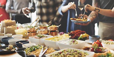 Il s'agit d'un buffet , on peut voir des pates, du céléri, du curry...Le buffet est contenu dans des bols blancs ou alors des petites cassolettes en cuivre. On peut voir des personnes habillés avec des chemises entrain de se servir. Un possède un verre de vin dans la main