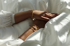 Layered gold filled bracelets on hand