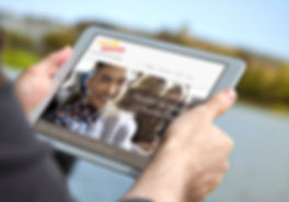 Man holding white iPad air in a park.jpg