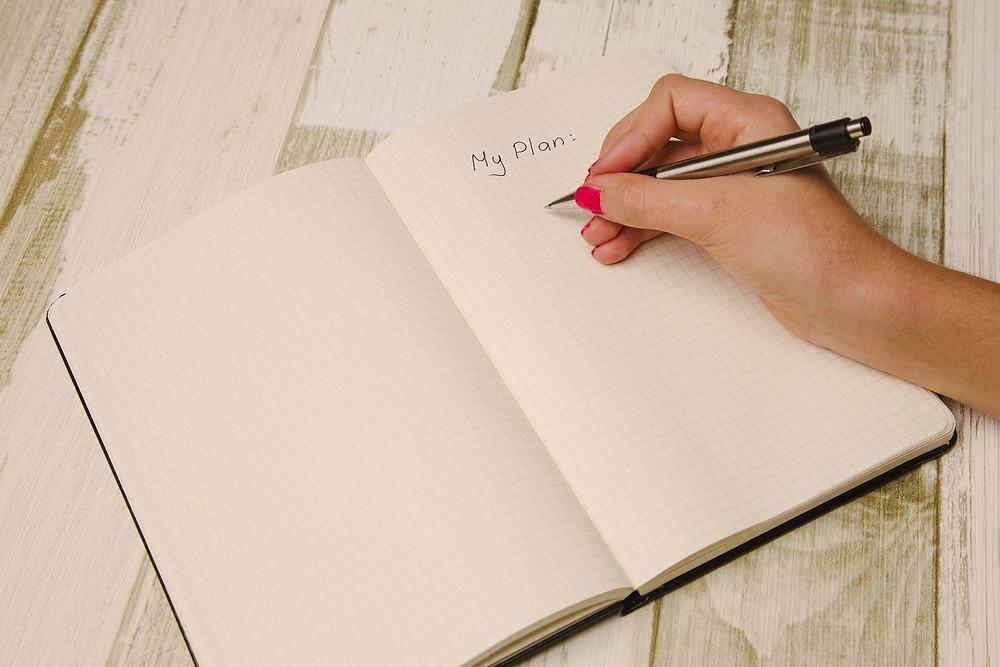 Mão femina segurando uma caneta, sobre uma agenda aberta, onde consta escrito: My Plan: