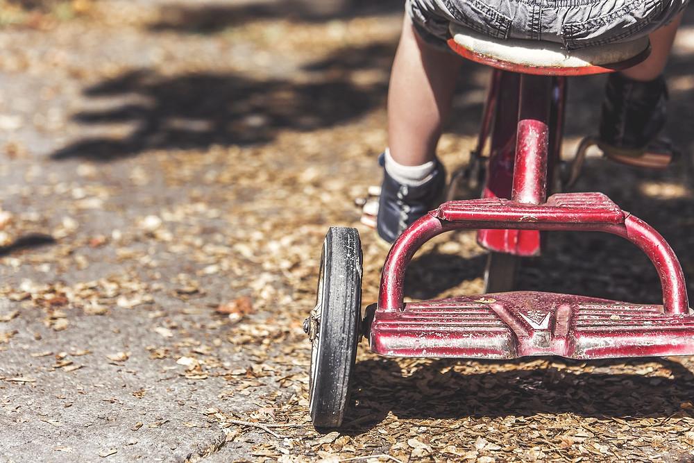 Parte traseira de um triciclo vermelho, com uma criança sentada, mostrando apenas suas pernas  e pés nos pedais e parte do assento. O chão está coberto de folhas secas, com sombra dos galhos das árvores.