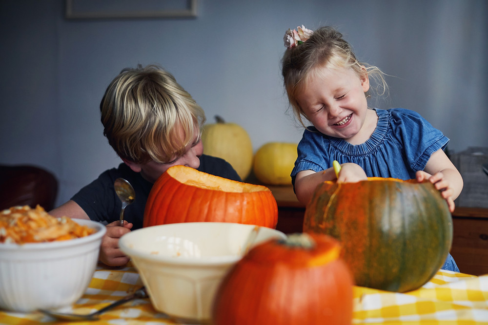 Kids carving out their pumpkins on a table
