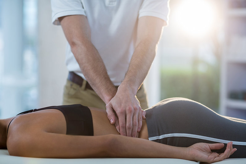 Male physiotherapist giving back massage