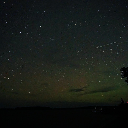 Meteor falling through auroras