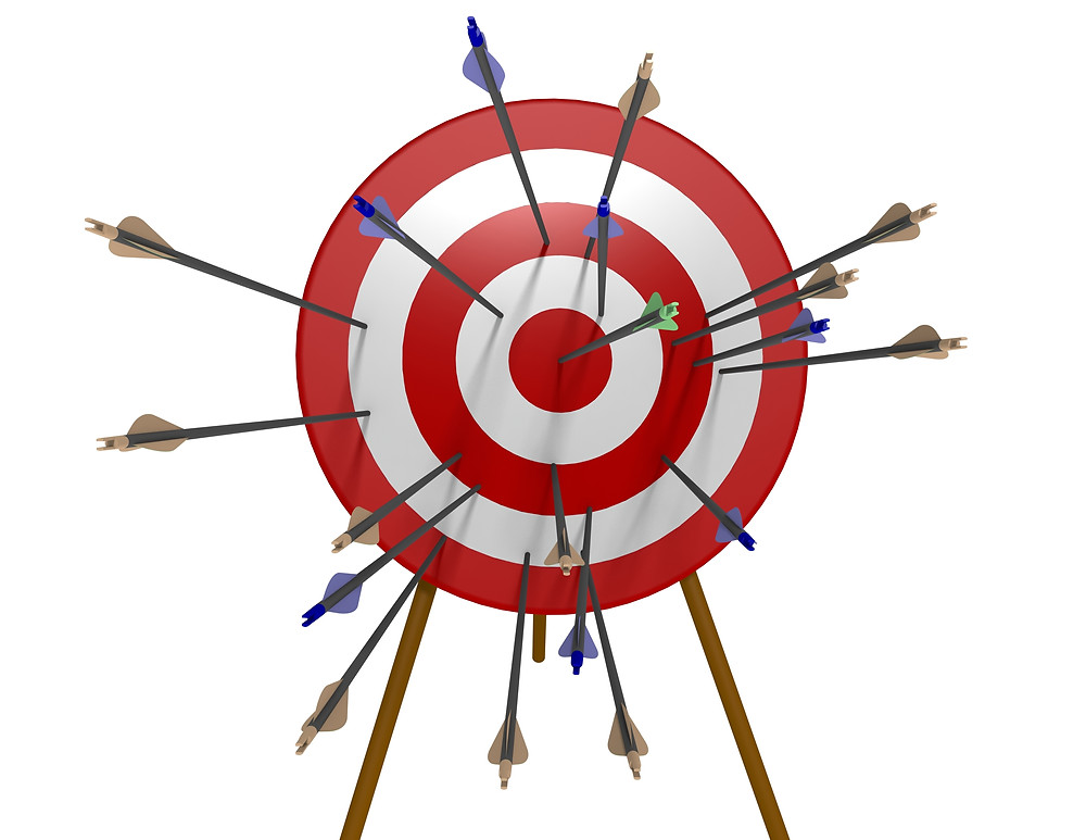 Round archery target with red and white circles and archery arrows all over target each arrow represents different business marketing tactic illustrates inefficiency of operating without strategy