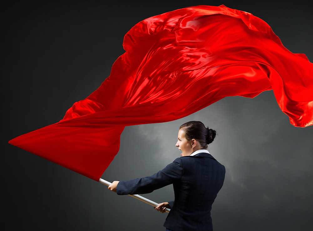 Big, bright red, flag, being waved aggressively, by woman in dark grey business suit, she screams to call attention to goal-setting mistakes made creating business plans