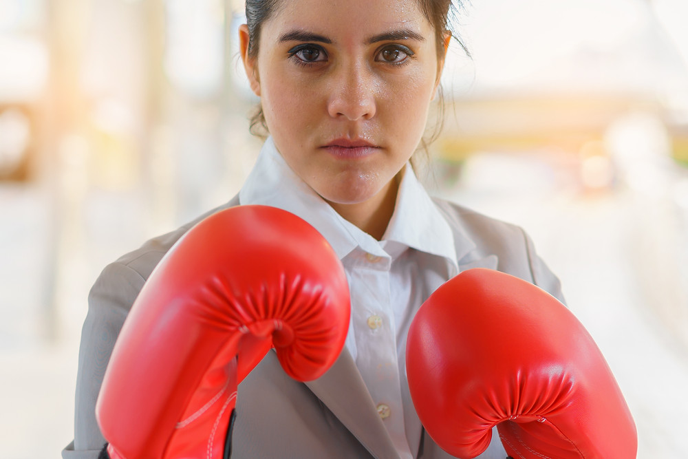 Professional female in business clothes wearing red leather boxing gloves raised and ready to fight illustrates conflict between accounting and managers during annual business marketing budgeting and planning process
