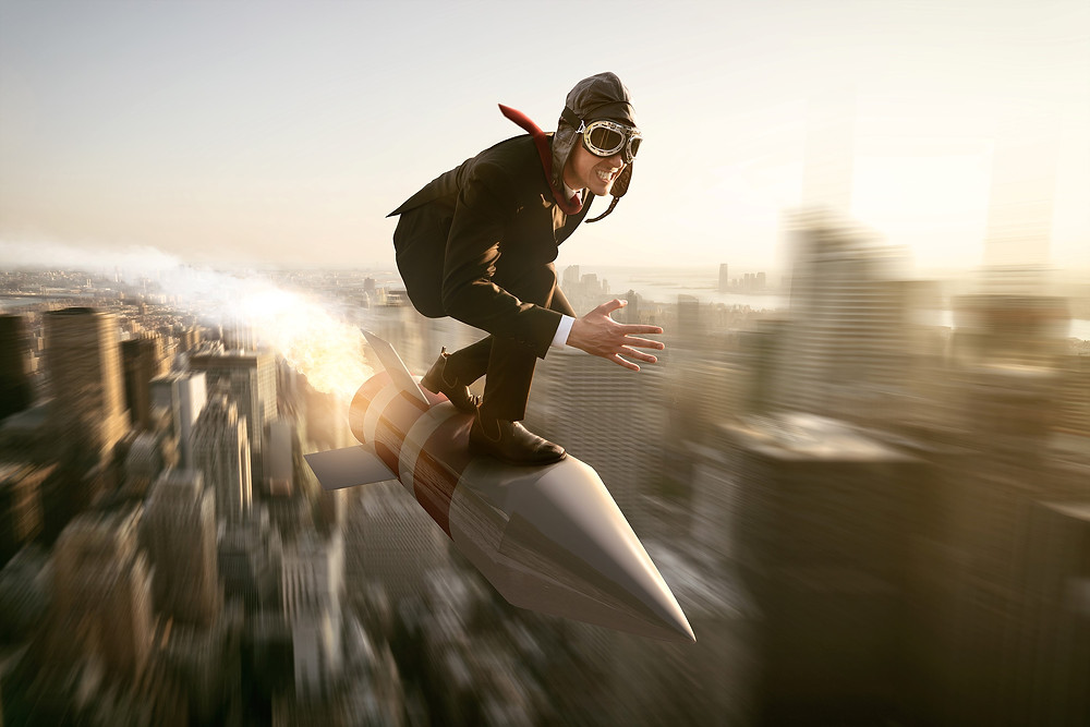 Business man, wearing suit plus pilots helmet and goggles, leaning forward in crouched position, balanced on rocket, flying very fast over the downtown area of a large city