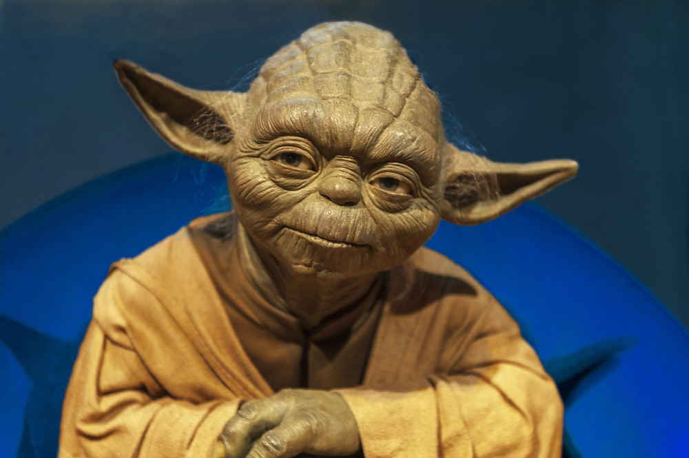 Master Yoda seated arms folded reflecting and offering wise mentoring advice
