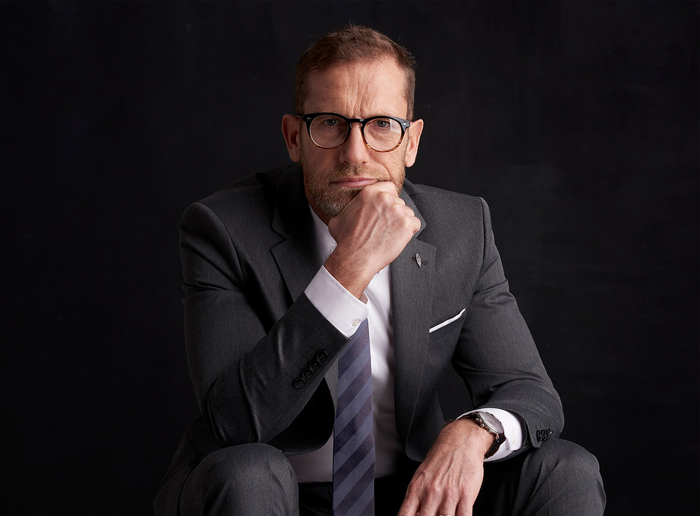 Chief Executive Officer, 50 years old, male, well dressed in gray suite with white shirt and striped tie, eye glasses, expensive watch, looking pensively directly into camera