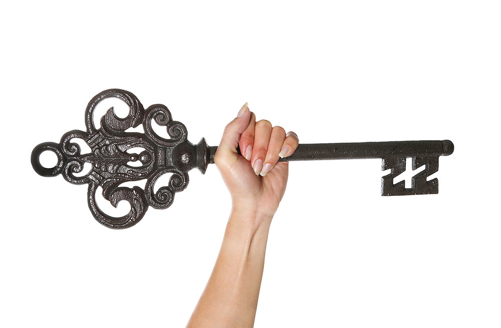 Woman's hand grasping a large ornamental iron key and raising it skyward