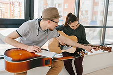 guitar teacher instructing student