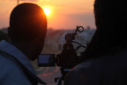 2 men looking through a camear viewfinder at sunset doing video production