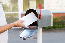 Man putting postcards with J29 Marketing logo in mailbox for direct mail marketing