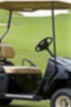 Golf cart on golf course near sand trap