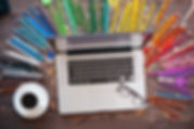 Computer with multi-colored pencils around it showing graphic design