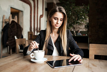 Lady in coffee shop on tablet looking for website design
