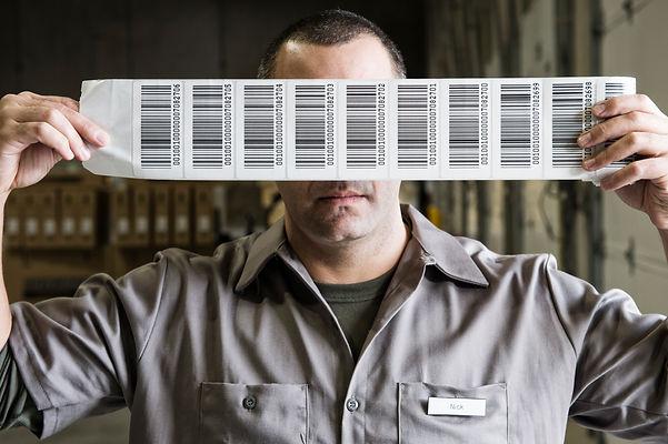 a-warehouse-worker-holding-up-a-sheet-of-bar-code--CZCEB4Z.jpg