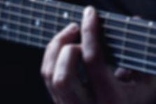 Mains sur les cordes de guitare