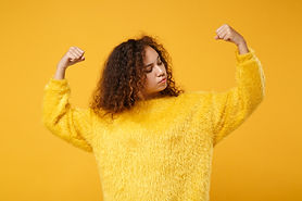Strong young african american girl in fur sweater posing isolated on yellow orange backgro